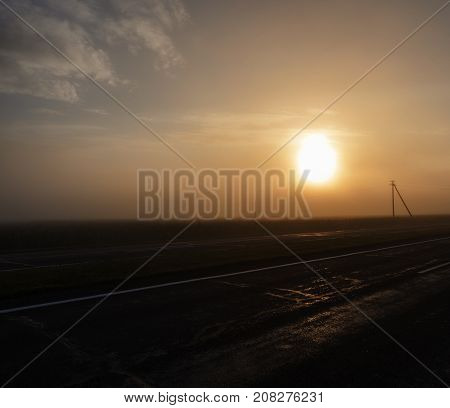 wet asphalt road, electric posts and fog during the sunrise. orange from a sunlight. landscape with poor visibility in the haze
