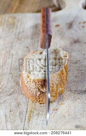 half-cut piece of baguette. in the bread sticking out a metal knife with a wooden handle. close-up photo on cutting board.