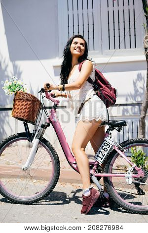 Beautiful georgian woman on pink bike, smiling. Tourist rent,summer travel