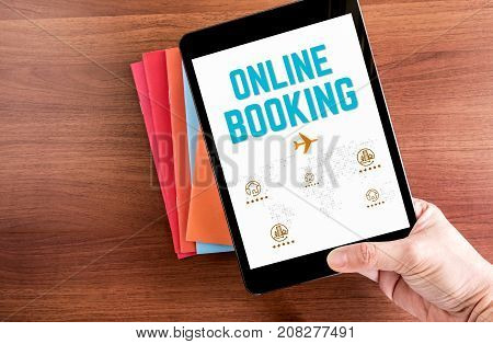 Top View Of Hand Holding Tablet With Online Booking Word With Icon Over Color Notebook On Wooden Tab