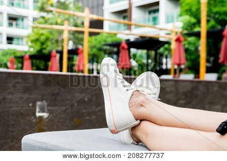 Close Up At Woman White Sneaker With Cross Legs Gesture At Sunbeds With Blur Pool Background.