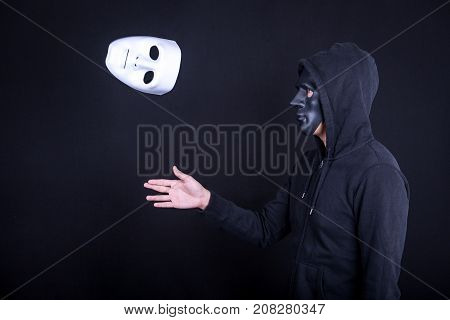 Mystery man wearing black mask throwing white mask. Anonymous social masking or halloween concept.
