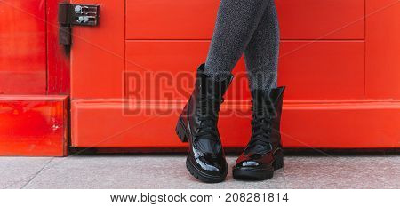 Red door and women's legs in black boots