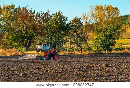 Farmer with tractor seeding - sowing crops at agricultural fields in autumn.