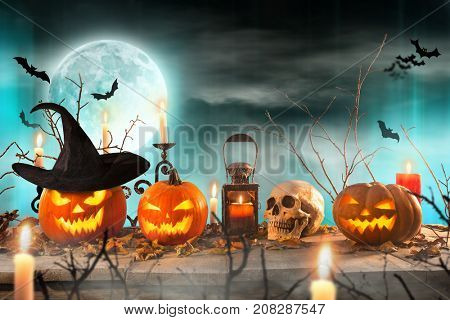 Spooky Halloween pumpkins on wooden planks with spooky background.