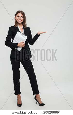 Full length portrait of a joyful young businesswoman in suit holding clipboard with documents and holding copy space on her palm isolated over white background