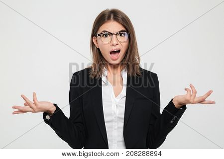 Portrait of a puzzled young businesswoman in suit and eyeglasses gesturing with hands isolated over white background