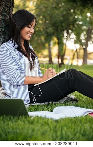 Pretty chinese female student listening to music, while studying in park outdoor