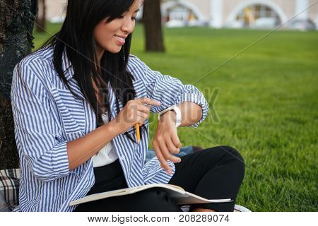 Young smiling asian student checking time, while sitting on grass, outdoor