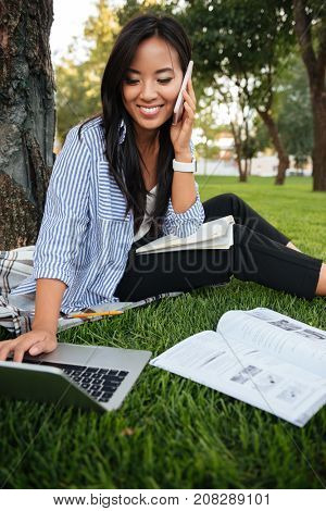 Happy asian female student sitting on grass with laptop and talking on phone in park, outdoor