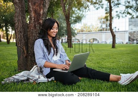 Beautiful young asian woman sitting under a tree and chatting on laptop, outdoor