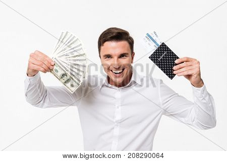 Portrait of a cheerful young man in white shirt showing bunch of money banknotes and a passport with flying tickets while standing isolated over white background