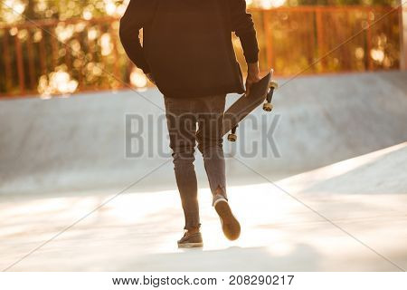 Cropped image of a young african man skateboarder walking with a skateboard at a city park