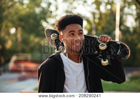 Young happy skateboarder man holding skateboard on his shoulders at public park