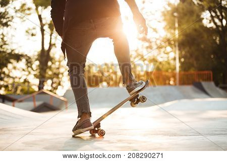 Close up of young male skateboarder training in skate park at sunset