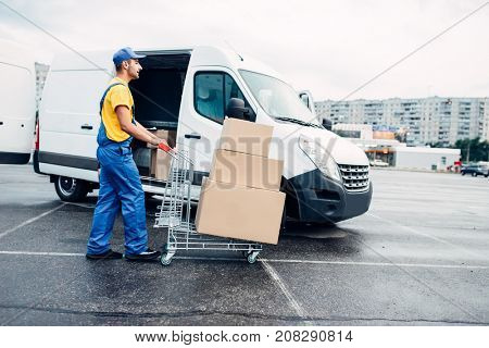 Courier with parcel trolley against logistic truck