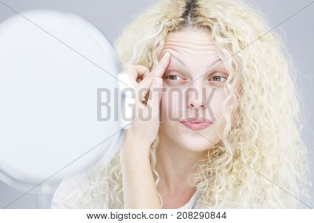 Blonde woman and mirror