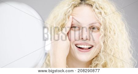 Blonde woman with curly and mirror