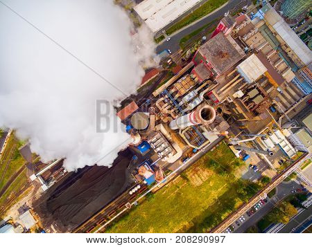 Aerial view to smoking chimmney from lignite power plant. Air pollution and climate change theme. Heavy industry from above.