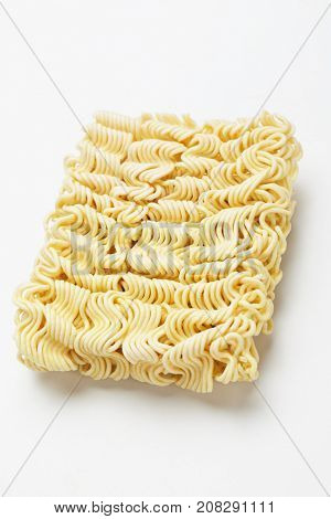Raw asian instant noodles shot over white background