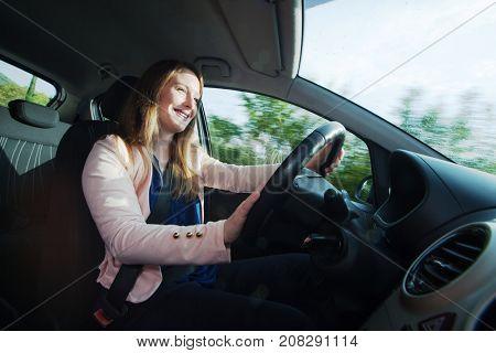 Young woman enjoys driving small passenger vehicle