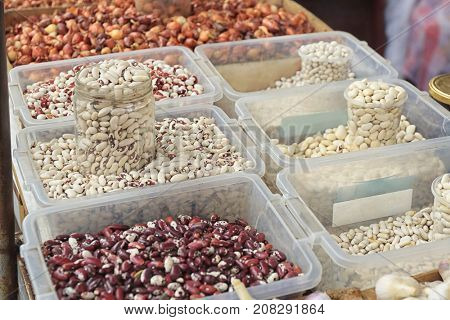 Assortment of beans in plastic containers at market