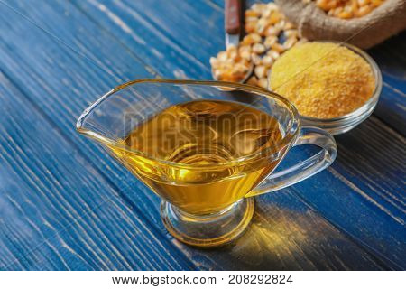 Glass gravy boat with corn oil on wooden background