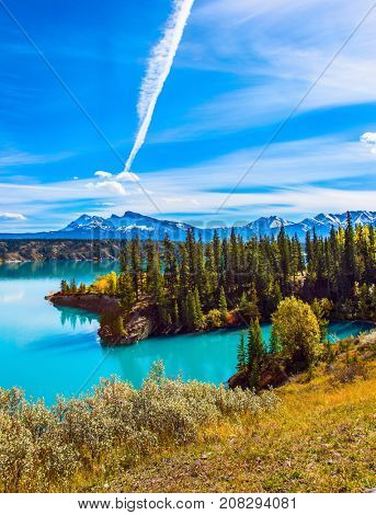 Rocky Mountains of Canada in the Indian summer. In the blue sky silver trace of the plane. Magnificent turquoise Abraham Lake. The concept of ecological and active tourism