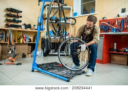 Repair specialist holding bicycle wheel over toolkit while checking it up