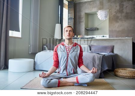 Young man in activewear trying to relax and concentrate on peace of mind