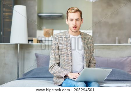 Young home-office manager with laptop sitting on bed and networking