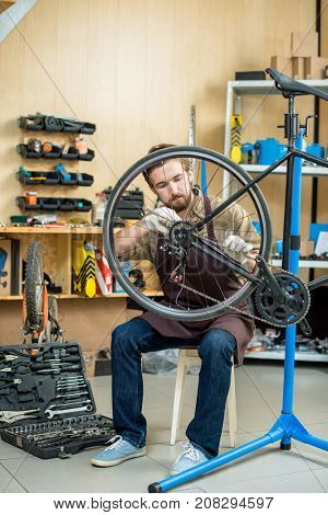 Master of repair in uniform sitting on chair and fixing wheel gear