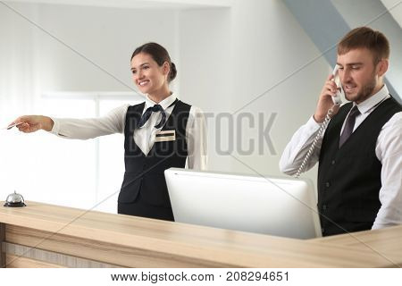 Two hotel receptionists at work