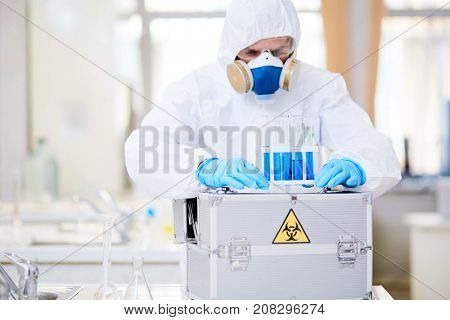 Concentrated scientist wearing hazmat suit examining test tubes while carrying out experiment at chemistry laboratory, blurred background