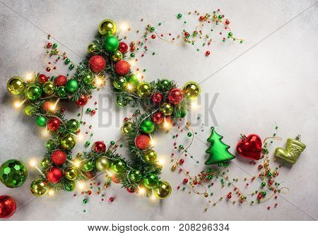 Decorative Christmas Star with colored baubles, christmas tree branches and lights. Top view.