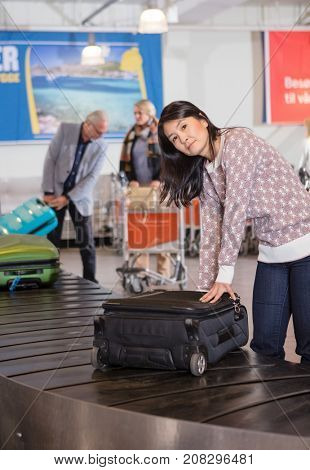 Woman Collecting Baggage At Conveyor Belt In Airport