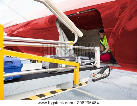 Worker Placing Baggage On Conveyor While Unloading Airplane
