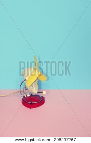 Vintage colorful portable home cooling fan on pastel background with space for copy.
