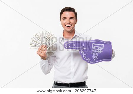 Portrait of a happy smiling man in white shirt holding bunch of money banknotes and wearing foam finger isolated over white background