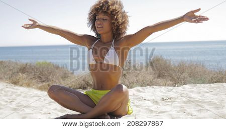 Beautiful fit woman in bikini and bright shorts sitting on sandy beach with eyes closed enjoying harmony of sea and sunlight.