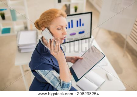 Mature salesperson with contract consulting clients on the phone