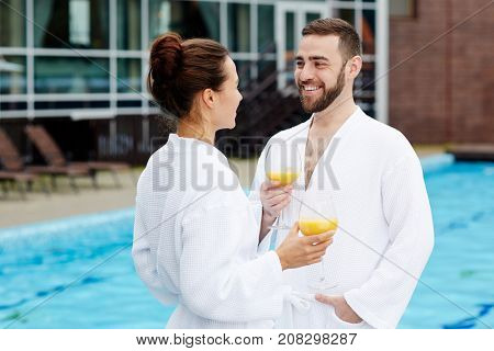 Romantic sweethearts with glasses of juice talking by swimming pool at spa resort