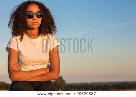 Beautiful mixed race African American girl teenager female young woman outside wearing sunglasses looking sad depressed or thoughtful at sunrise or sunset