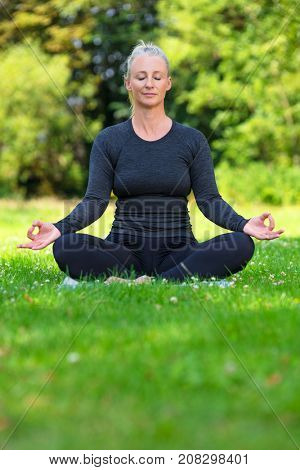 Mature middle aged fit healthy woman practicing yoga kapalbhati pranayama position outside in a natural tranquil green environment