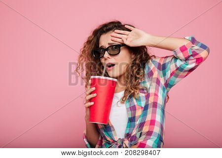 Young frightned caucasian woman in 3d glasses with cola afraid of film isolated over pink