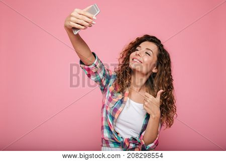 Young beautiful woman in casual clothes making selfie on smartphone and showing thumb up gesture isolated over pink
