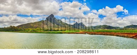 Beautiful landscape. View of a sugarcane, irrigation pond and mountains. Mauritius island. Panorama