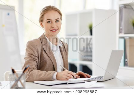 Pretty young accountant sitting by desk, planning work and browsing in the net