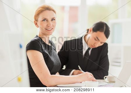 Confident business leader organizing work on background of her subordinate