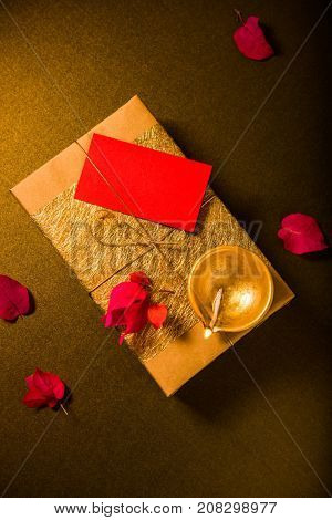 Empty tag placed on a beautiful golden gift box, arranged with an earthen lamp on the occasion of Diwali - a festival of light. View from above.